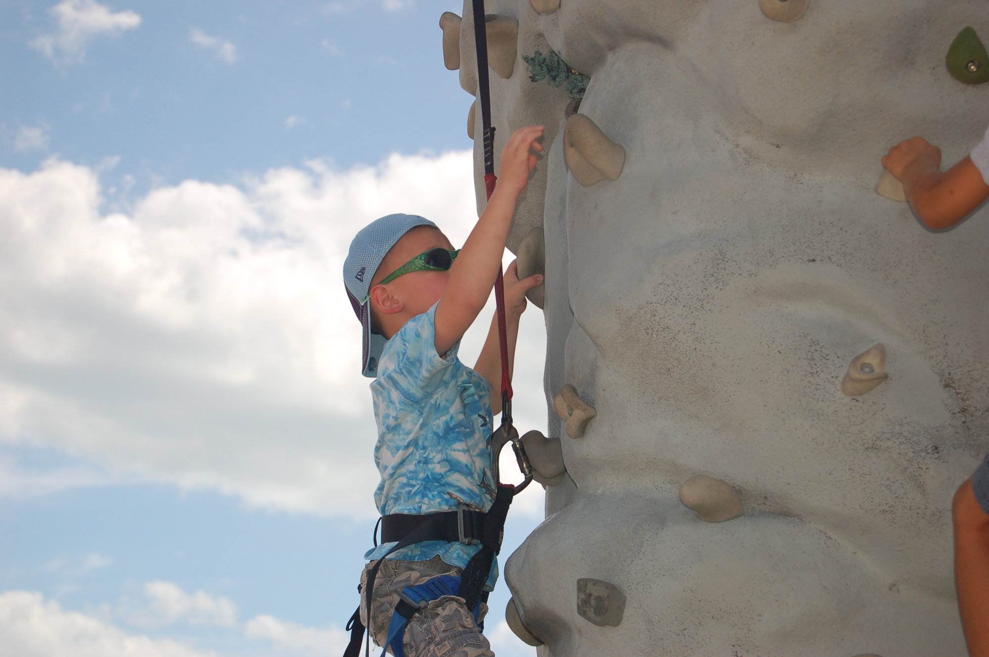 Boy ascends rock climbing wall